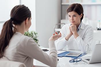Ärztin und Frau führen Gespräch