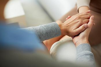 Personen halten sich die Hände