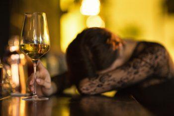 Frau schläft an Bar mit Wein in der Hand