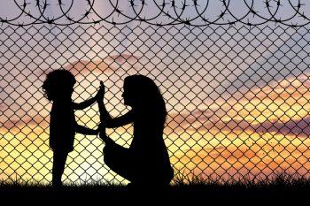 Frau und Kind stehen vor Stacheldrahtzaun und legen die Hände aneinander