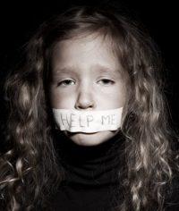 """Kind mit Zettel am Mund ,,Help me"""""""